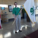 4-Her holding the 4-H flag