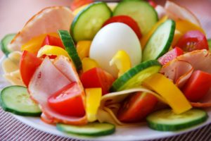 A photo of various sliced vegetables (radish, cucumbers, tomatoes, bell peppers)