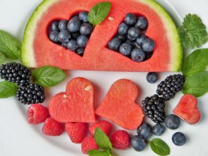 Plate of fruit with pieces of watermelon in shape of hearts.