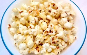 Close up photo of popcorn in a white bowl with a blue rim.
