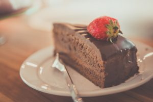 Photo of a slice of chocolate cake topped with a strawberry